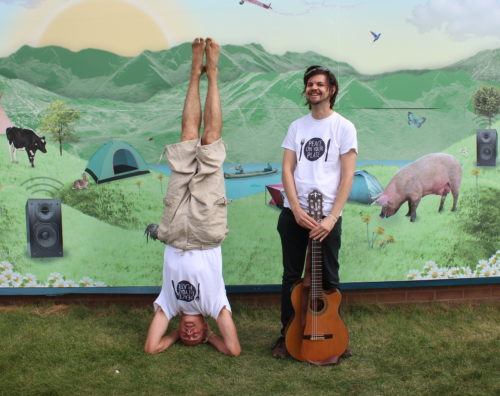 Songwriters Giles Bryant (headstand) and Gavin Chappell-Bates (guitar)